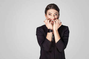 worry businesswoman gnawing nails and looking at camera with hope on grey background