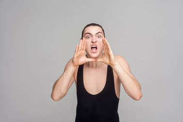 anger man with big eyes screaming at camera on gray  background