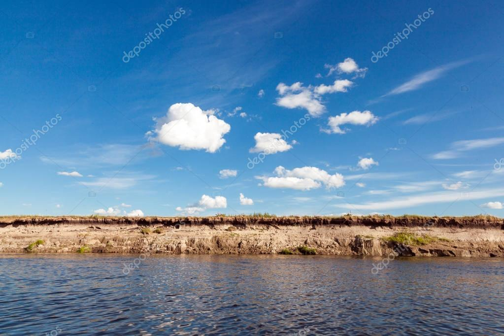 panoramic view of riverbank with reflections of white fluffy clouds and blue sky on ripple water surface