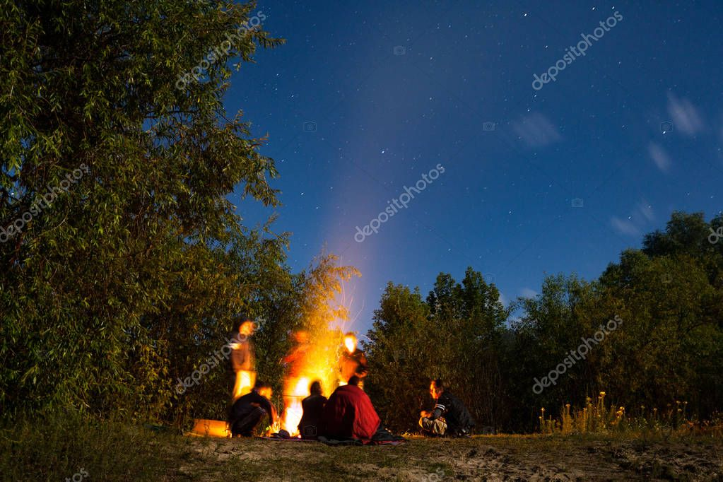tourists sitting around big bright bonfire on sandy beach at night