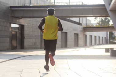 young fit man wearing yellow color sportswear running fast outdoors, sport concept