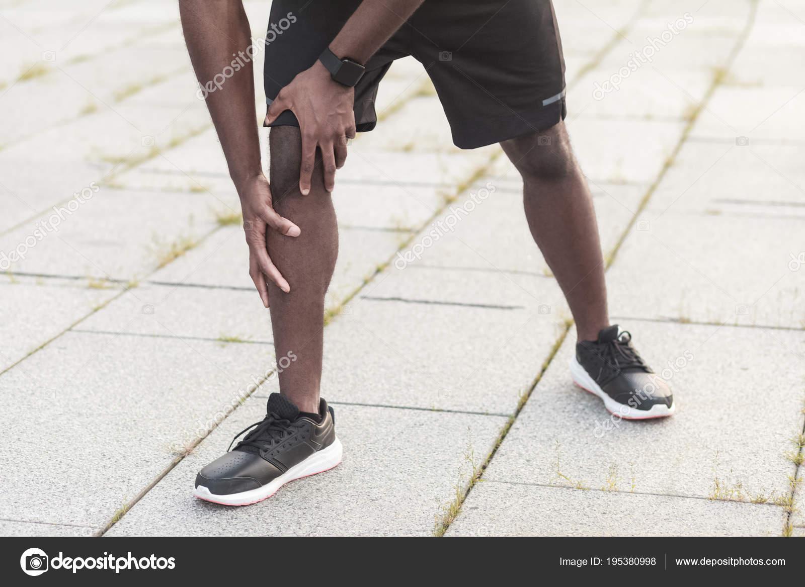 Uomo afroamericano toccando gamba mentre piedi sul concetto