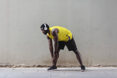 african american runner in yellow sportswear stretching before doing morning workout