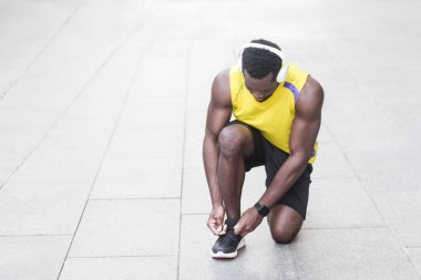 sporty man tying up shoelaces on sneakers before running at street