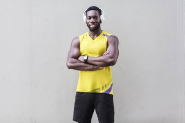 african american man with perfect muscled body in headphones standing with crossed arms and looking at camera on gray background
