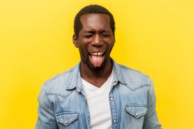 Portrait of positive carefree young man showing out his tongue.