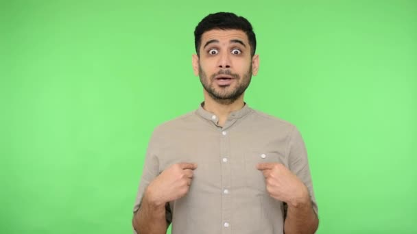 This is me? Brunette man with bristle in shirt pointing himself and looking shocked, pleasantly surprised by success, shouting from happiness and amazement. studio shot, green background, chroma key