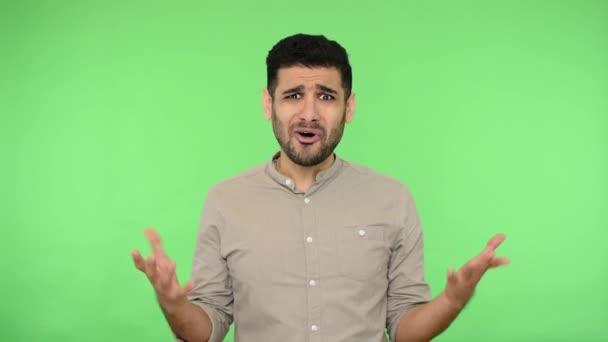 Zoufalý bruneta muž s naježenou košilí zvedá ruce v zoufalství a ptá se, proč, co chcete, vypadá frustrovaný, rozhořčený výraz. vnitřní studio natáčení, zelené pozadí, chroma klávesa