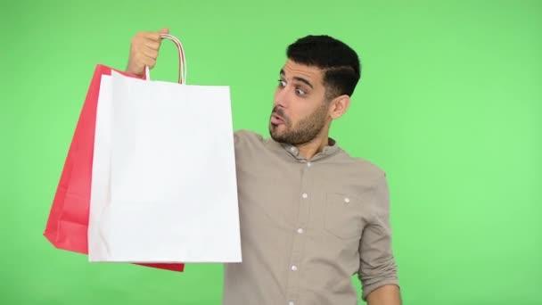 Šťastný užaslý kupec v košili ukazující prstem na nákupní tašky a tvářící se šokovaně, příjemně překvapený nákupem, ukazující palce nahoru, jako gesto. interiér studio záběr, chroma klávesa