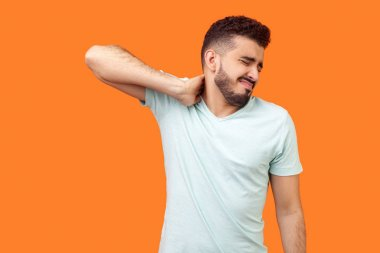 Portrait of exhausted brunette man with beard in white t-shirt rubbing his neck and grimacing from pain, suffering muscle tension, shoulder hurts. indoor studio shot isolated on orange background stock vector