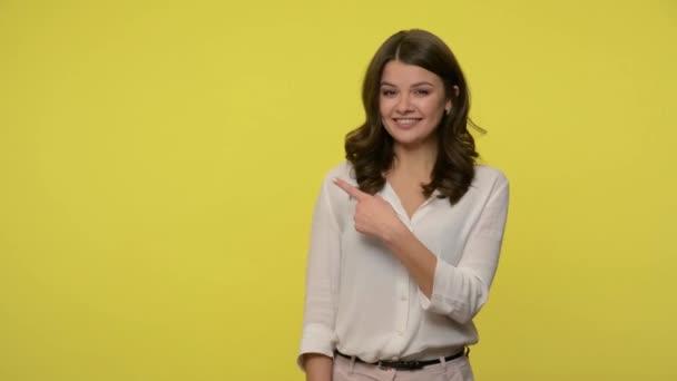 freundliche positive Frau mit brünetten Haaren in Bluse zeigt auf leeren Platz und lächelt in die Kamera, zeigt Kopierraum für Werbetext, Werbefläche. Innenaufnahmen im Studio, gelber Hintergrund