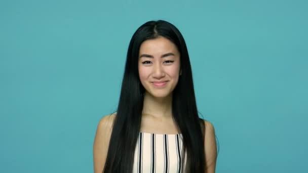 Okouzlující asijská žena s dlouhými rovnými černými vlasy, která hravě mrká a usmívá se, flirtuje s kamerou, má nějaký mazaný nápad, mrká okem. vnitřní studio záběr izolované na modrém pozadí