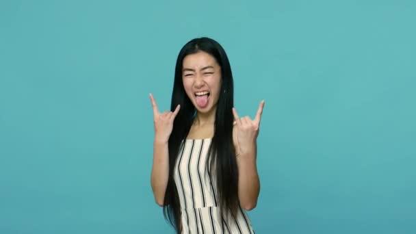Lelkes, izgatott ázsiai nő hosszú, egyenes fekete hajjal ruhában, rock and roll punk felirattal, ördögszarvas gesztussal őrült arckifejezéssel. beltéri stúdió lövés elszigetelt kék háttér