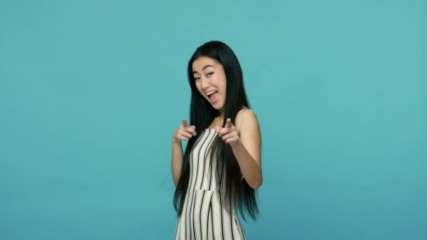 Hey, you are awesome! Cheerful woman with long straight black hair in dress pointing to camera and looking with playful happy expression, making choice, showing direction. studio shot, blue background