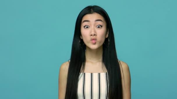 Amüsante, fröhliche Asiatin mit langen schwarzen Haaren, die Fischgesicht-Grimasse mit schmollenden Lippen zeigt, herumalbert und lächerlich kindisch-schelmischen Humor zeigt. Studioaufnahme isoliert auf blauem Hintergrund