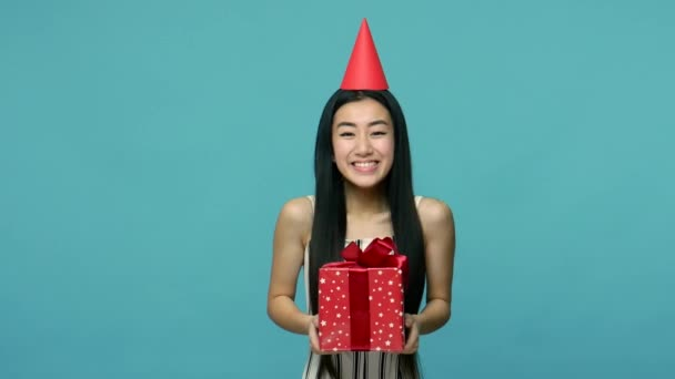 Confetti falling on excited asian woman with funny party cone on head, girl holding present box and accepting greetings on her birthday, party celebration. studio shot isolated on blue background