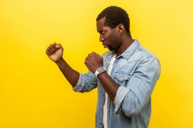 Side view portrait of confident purposeful man in denim casual shirt standing in defensive posture with clenched fists attack, ready to fight, attack. indoor studio shot isolated on yellow background stock vector