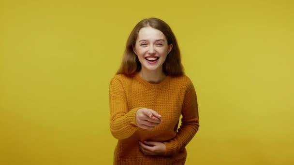 amüsiertes fröhliches Mädchen mit braunen Haaren im Pullover, das ihren Bauch hält, während es hysterisch lacht und in die Kamera zeigt, spottet, sich über dich lustig macht. Innenstudio isoliert auf gelbem Hintergrund aufgenommen