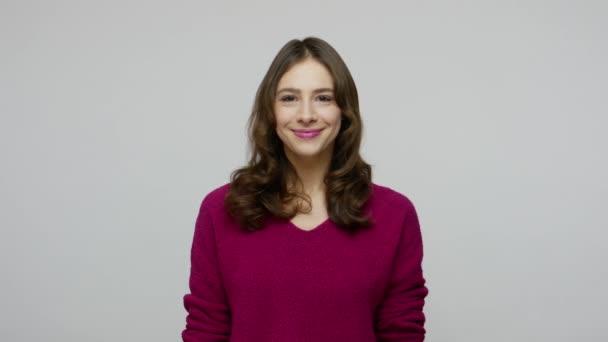 Veselá hezká žena s hnědými vlasy ve svetru dívá do kamery s poutavým úsměvem, optimistický radostný výraz