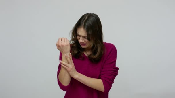 Frustrated woman rubbing injured hand with painful facial expression, massaging sore wrist,