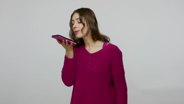 Brunette woman in pullover making voice records on mobile phone, talking to smart device giving command