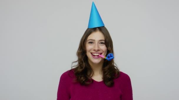 Gratulálok a sikerhez! Boldog barna nő vicces kúp a fej fúj party kürt, gratuláló karrier növekedés
