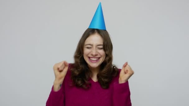 Excited brunette woman pointing at funny cone on her head, having fun and dancing, rejoicing at birthday party