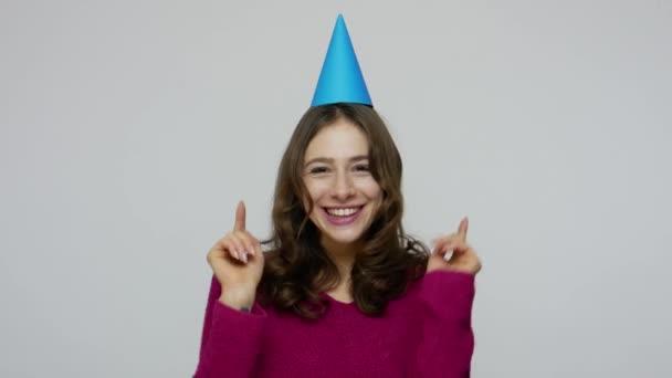 Nadšený šťastný brunetka dívka tanec s party kužel na hlavě, chytání dárek box říká wow, překvapen přítomností
