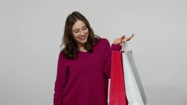 Joyful enthusiastic shopper, happy woman holding Sale inscription and shopping bags
