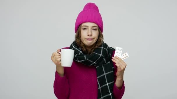 ungesunde Frau in Wintermütze und Schal mit unzufriedenem kranken lustigen Gesichtsausdruck, hustend
