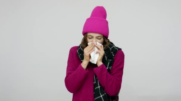 Unhealthy girl in winter hat and scarf sneezing in napkin and looking with displeased sick funny face expression