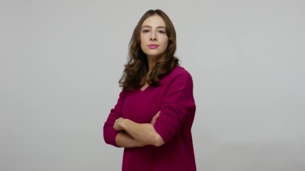 Pozitivní atraktivní brunetka žena otáčí na kameru se zkříženýma rukama a dívá se s poutavým úsměvem