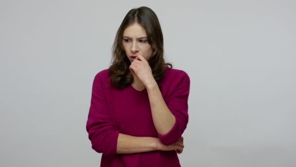 Confused thoughtful brunette woman in pullover biting lips from anxiety while pondering with perplexed expression