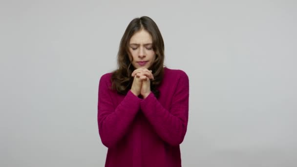 Please, God! Worried brunette woman in pullover praying heartily and looking up with imploring face