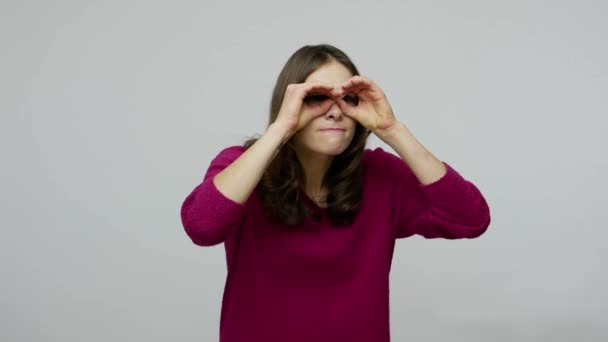Brunette woman with funny grimace exploring world around, looking through fingers in binoculars gesture