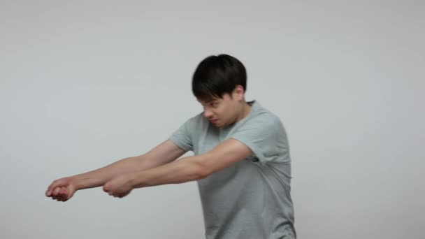 Young ambitious guy in T-shirt holding invisible rope and pulling his burden with great effort, metaphor for difficult path to success, strivings and motivation. Indoor studio shot gray background.