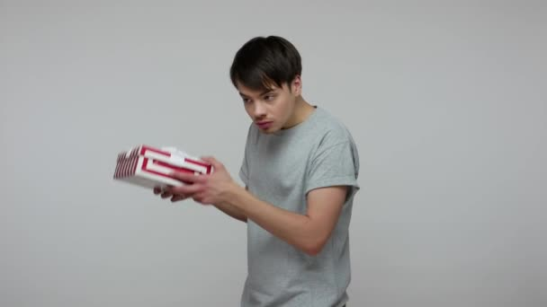 Young impatient guy in casual t-shirt shaking wrapped gift, listening to guess what's inside box, curious about interesting present, bonus or surprise. indoor studio shot isolated on gray background
