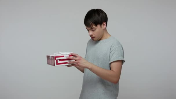 Wow, I like present! Happy lucky brunette man in T-shirt unpacking long-awaited gift box and looking amazed overjoyed, satisfied with birthday surprise. indoor studio shot isolated on gray background