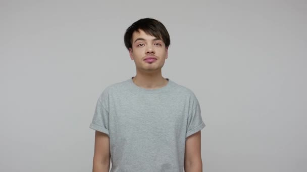 Happy young ambitious student guy in casual T-shirt dreaming of successful future career and smiling, having optimistic fantasies, positive memories. indoor studio shot isolated on gray background
