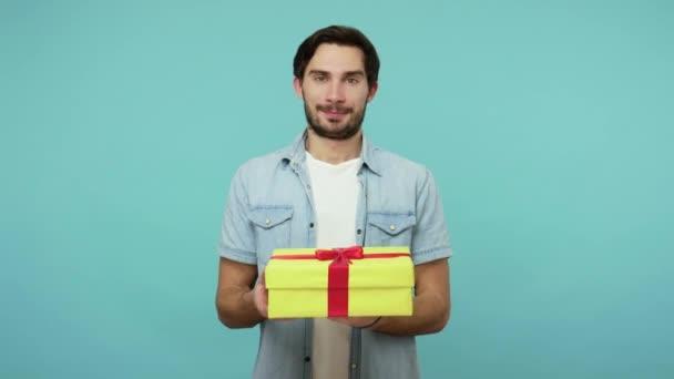 Tenhle dárek pro tebe! Hezký vousatý chlapík v džínové košili dává krabici na kameru, laskavě se usmívá a nabízí dárek k narozeninám, vánoční svátky. studio záběr izolované na modrém pozadí
