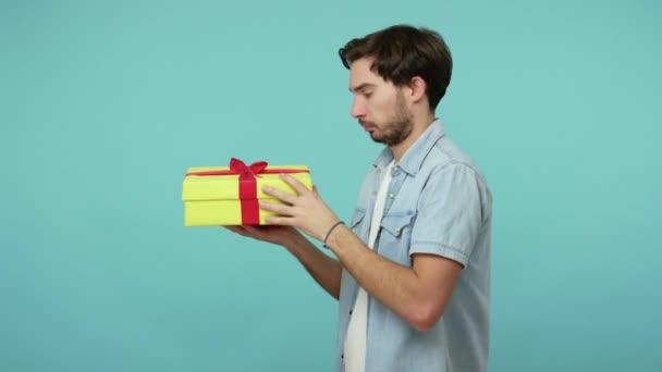 Vousatý chlapík v džínové košili držící dárek a třesoucí se krabici se zájmem, rozbaluje a raduje se z dlouho očekávaného dárku, potěšen narozeninovým překvapením. vnitřní studio záběr izolované na modrém pozadí