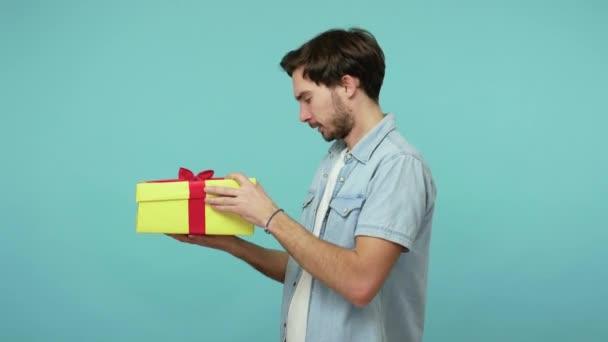 Kedves fickó kicsomagolja az ajándékot és extrém örömöt fejez ki, elégedett a tökéletes szülinapi meglepetéssel, átöleli a dobozt, azt mondja boldog vagyok, ünnepli az ünnepeket. beltéri stúdió lövés elszigetelt kék háttér