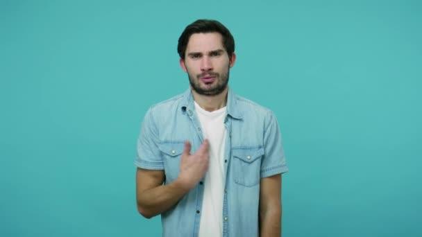 Co ode mě chceš? Rozzuřený vousáč v džínové košili vypadal zmateně, rozpačitě pokrčil rameny a zeptal se proč. studio záběr izolované na modrém pozadí