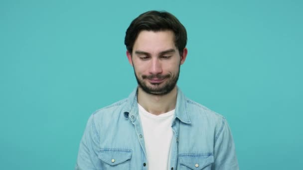 Comical stupid bearded guy in jeans shirt looking cross-eyed and making funny awkward silly grimace, playing fool, pretending to be dumb, brainless. indoor studio shot isolated on blue background