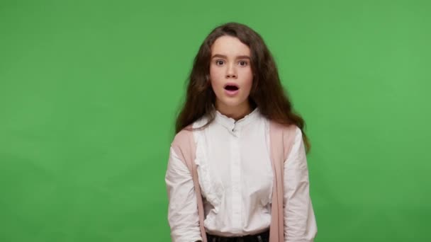 Amazed impressed teen brunette girl in white shirt looking with mouth open in surprise, shocked by crazy news, unexpected winning result, disbelief reaction. studio shot isolated on green background