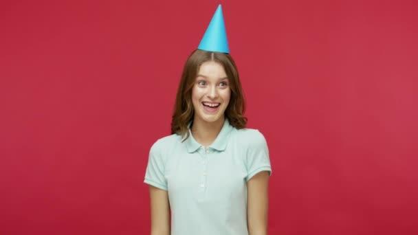 Ünnepi hangulat. Boldog fiatal barna nő pólóban és vicces kúp a fej fújás party kürt, ünnepli születésnapját és gratulál az ünnepek. beltéri stúdió lövés elszigetelt piros háttér