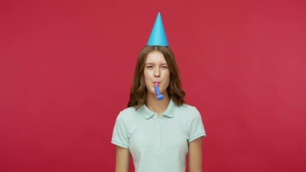 Narozeninové překvapení. Šťastná mladá brunetka v polo tričku a legrační kužel na hlavě troubení party rohu a chytání dárkové krabice, slaví svátky. vnitřní studio záběr izolované na červeném pozadí