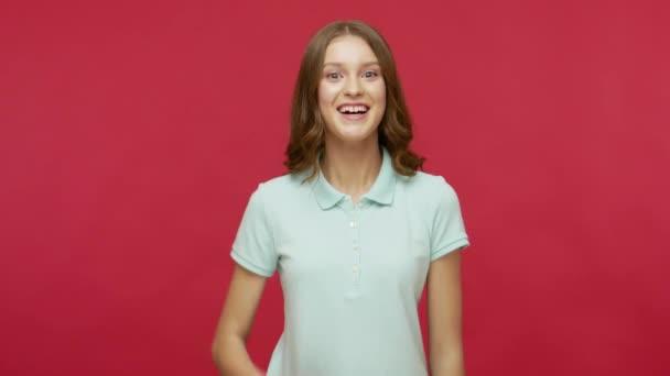 Freundliche junge brünette Frau im Polo-T-Shirt, die die Hand ausstreckt, Händedruck anbietet und mit zahmem Lächeln begrüßt wird, mit gastfreundlichem, positivem Ausdruck. Indoor-Studio isoliert gedreht