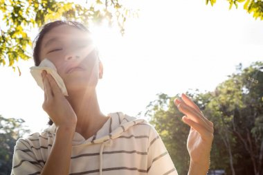 Asian child girl wiping sweat on her face with tissue paper suffer from sunburn very hot in summer weather problem feel faint, tired female teenage with heat stroke,high temperature on sunny day