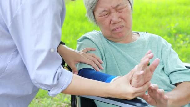 Zraněná asijská starší žena s podpěrou lokte trpící bolestí svalů, bolestí paží lokte, ošetřovatelka nemá v úmyslu masírovat tvrdé, nešťastné starší ženy s chrániči loktů pocit bolesti